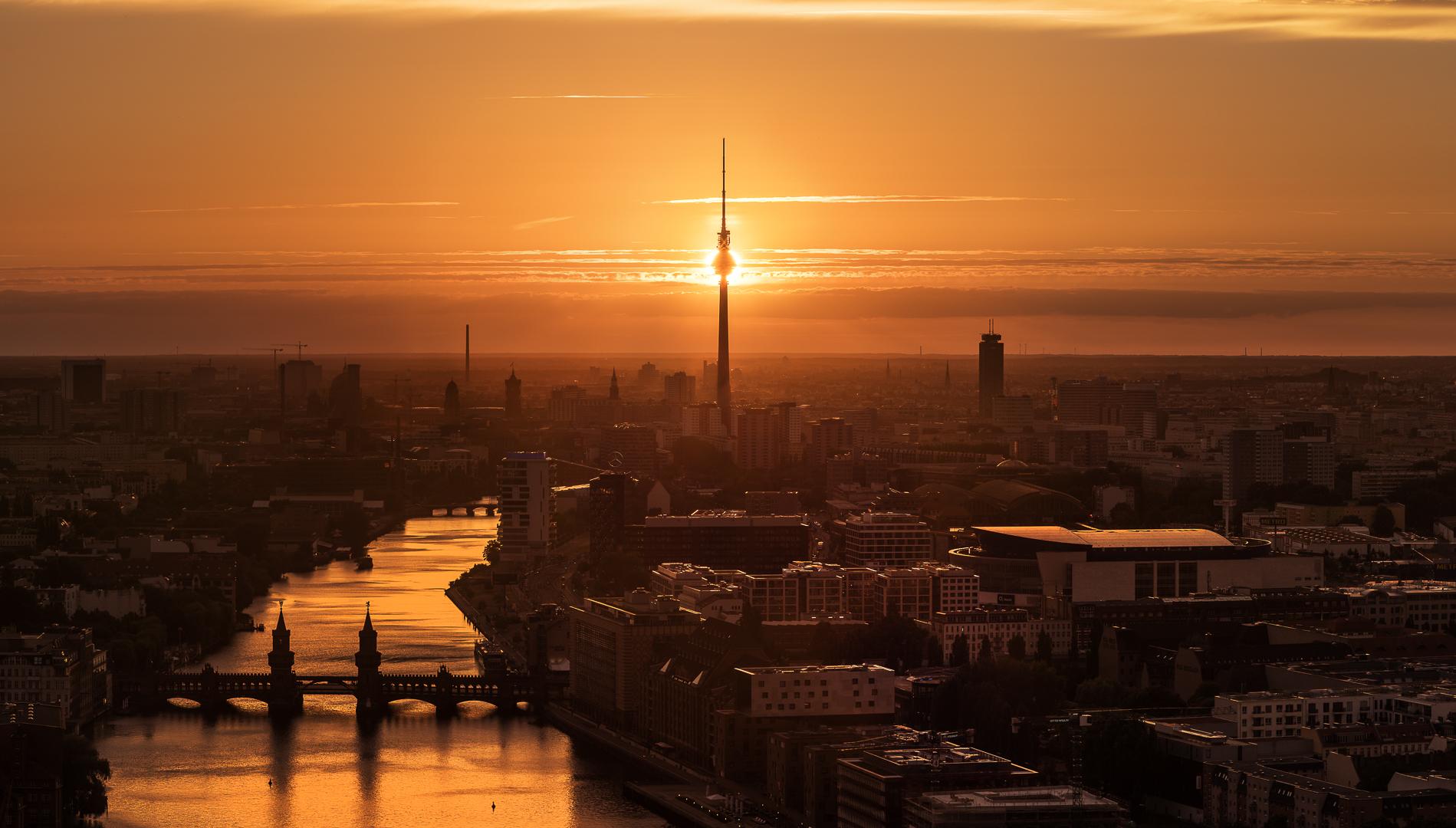 Die untergehende Sonne hinter dem Fernsehturm in Berlin als Panorama